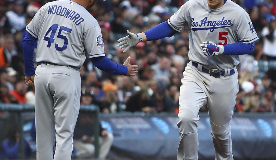 Los Angeles Dodgers' Corey Seager, right, is congratulated by third base coach Chris Woodward (45) after hitting a two-run home run off San Francisco Giants' Johnny Cueto in the first inning of the second game of a baseball doubleheader Saturday, April 28, 2018, in San Francisco. (AP Photo/Ben Margot)