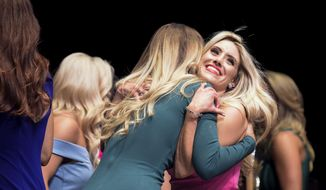 In an April 19, 2018 photo, Dana Pasqualone, right, a councilwoman in Washington Township, is hugged by Victoria LaRocca of South Jersey as they stand onstage as official Philadelphia Eagles cheerleaders following tryout finals at the Kimmel Center in Philadelphia. (Joe Lamberti/Camden Courier-Post via AP)