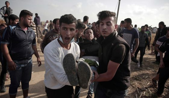 FILE - In this April 27, 2018, file photo, Palestinians carry a wounded man during a protest at the Gaza Strip's border with Israel. The Supreme Court on Monday, April 30, heard the first legal challenge of the Israeli military's open-fire rules, after at least 39 Palestinians were killed and more than 1,700 wounded by Israeli fire during mass protests on the Gaza border over the past month. (AP Photo/ Khalil Hamra, File)