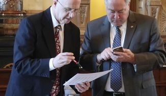 J.G. Scott, left, the Kansas Legislature's chief fiscal analyst, and Senate Majority Leader Jim Denning, right, R-Overland Park, confer after the Senate's approval of budget legislation, Monday, April 30, 2018, at the Statehouse in Topeka, Kan. The legislators approved by senators would restore past spending cuts in the state's higher education system. (AP Photo/John Hanna)