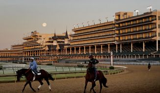 The full moon sets beyond the grandstands at Churchill Downs as horses work on the track Monday, April 30, 2018, in Louisville, Ky. The 144th running of the Kentucky Derby is scheduled for Saturday, May 5. (AP Photo/Charlie Riedel)