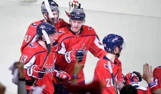 Washington Capitals' Nicklas Backstrom (19), of Sweden, celebrates his empty net goal with Tom Wilson (43), John Carlson (74), and Lars Eller (20), during the third period in Game 2 of an NHL second-round hockey playoff series against the Pittsburgh Penguins, Sunday, April 29, 2018, in Washington. The Capitals won 4-1. (AP Photo/Nick Wass)