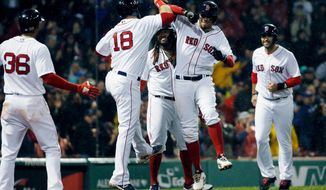 Boston Red Sox's Xander Bogaerts, center right, celebrates his grand slam that also drove in Mitch Moreland (18), Hanley Ramirez, behind and J.D. Martinez, right, during the third inning of a baseball game against the Kansas City Royals in Boston, Monday, April 30, 2018. (AP Photo/Michael Dwyer)
