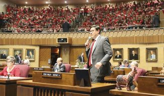 Arizona state Sen. Steve Farley, standing, introduces teachers from his Tucson district who were among those packing the Senate gallery while striking for better pay and school funding in Phoenix, Ariz., Monday, April 30, 2018. (AP Photo/Bob Christie)