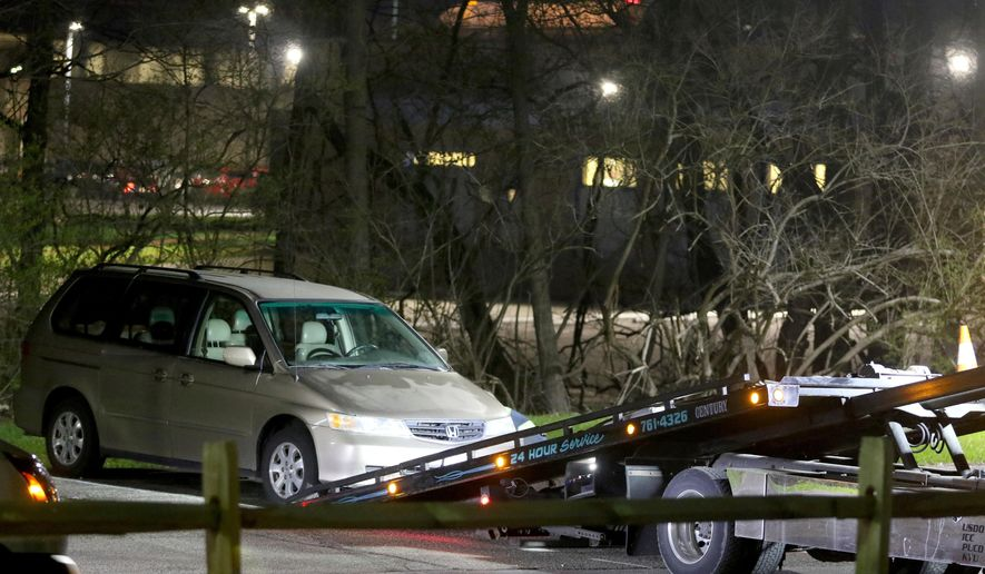 In this April 10, 2018, photo, a minivan is removed from the parking lot near the Seven Hills School campus in Cincinnati. Cincinnati officials expect to review a plan for improving the city's emergency center while police finish an internal investigation into the death of Kyle Plush who twice called 911 to report he was trapped in a minivan. (Cara Owsley/The Cincinnati Enquirer via AP, File)
