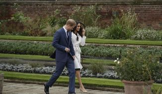 FILE - In this Nov. 27, 2017, file photo, Britain's Prince Harry and his fiancee Meghan Markle pose for photographers during a photocall in the grounds of Kensington Palace. Fans of the British royals will want to include castles, Westminster Cathedral and other sites connected to Queen Elizabeth II and her family on any trip to England. (AP Photo/Matt Dunham, File)