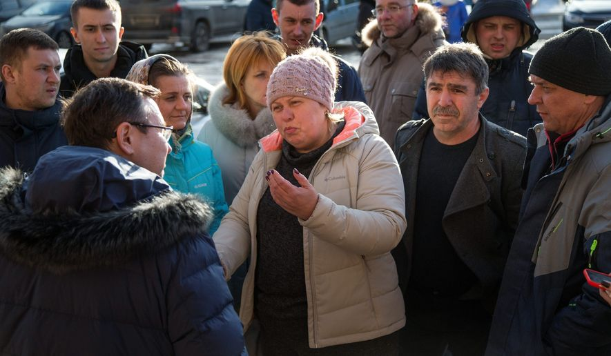 In this photo taken on Thursday, March 22, 2018, locals argue with a local administrator about the reported air poisoning in Volokolamsk, 100 kilometers (62 miles) west of Moscow, Russia. A gas poisoning linked to a toxic landfill in Volokolamsk, a town outside Moscow, left dozens hospitalized, prompting the regional governor to promise to evacuate local children from the area. (AP Photo/Alexander Zemlianichenko)
