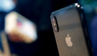 FILE- In this Nov. 3, 2017, file photo, the Apple iPhone X sits on display at the new Apple Michigan Avenue store along the Chicago River in Chicago. Apple Inc. reports earnings Tuesday, May 1, 2018. (AP Photo/Charles Rex Arbogast, File)