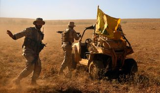 FILE - In this July 29, 2017 file photo, Hezbollah fighters stand near a four-wheel motorcycle positioned at the site where clashes erupted between Hezbollah and al-Qaida-linked fighters in Wadi al-Kheil or al-Kheil Valley in the Lebanon-Syria border. Facing a second suspected Israeli strike killing Iranian forces in Syria, the Islamic Republic has few ways to retaliate as its officials wrestle both domestic unrest at home and the prospects of its nuclear deal collapsing abroad. (AP Photo/Bilal Hussein, File)