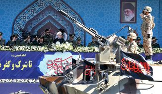 In this Sept. 22, 2017 file photo, Iran's President Hassan Rouhani, center, reviews a military parade during the 37th anniversary of Iraq's 1980 invasion of Iran, in front of the shrine of the late revolutionary founder, Ayatollah Khomeini, just outside Tehran, Iran. (AP Photo/Ebrahim Noroozi, File) **FILE**