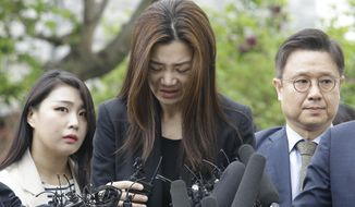 Former Korean Air Senior Vice President Cho Hyun-min, center, speaks as she arrives at a police station in Seoul, South Korea, Tuesday, May 1, 2018. The Korean Air heiress has apologized in her first public appearance as a suspect in an abuse of power case as public calls urging her family to resign grow. (AP Photo/Ahn Young-joon)