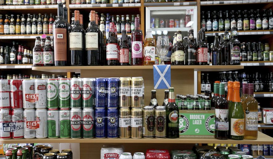 Shelves of alcoholic drinks are displayed for sale in an Edinburgh off-licence as Scotland has become the first country in the world to introduce minimum unit pricing for drinks, in Edinburgh, Scotland, Tuesday May 1, 2018. Health campaigners welcomed the change, saying minimum pricing for alcohol will save lives and money. (Jane Barlow/PA via AP)