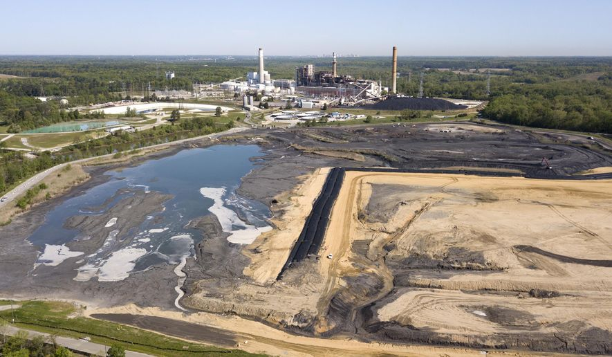 The Richmond city skyline can be seen on the horizon behind the coal ash ponds near Dominion Energy's Chesterfield Power Station in Chester, Va., Tuesday, May 1, 2018. Virginia's governor says the state has no plans to change its coal ash management practices, despite an Environmental Protection Agency proposal that would roll back federal regulations governing the byproduct generated by coal-burning power plants. (AP Photo/Steve Helber)