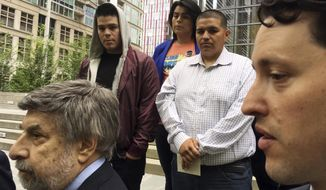 Daniel Ramirez Medina, center right in light-colored shirt, listens as two of his lawyers, Mark Rosenbaum, left, and Nathaniel Bach, right, address reporters following a hearing in U.S. District Court in Seattle on Tuesday, May 1, 2018. Ramirez is asking U.S. District Judge Ricardo S. Martinez to block the government from revoking his participation in the Deferred Action for Childhood Arrivals program, which allows those brought to the U.S. illegally as children to remain in the country to work or study. (AP Photo/Gene Johnson)