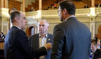 Kansas House Taxation Committee Steven Johnson, left, R-Assaria, confers with House Majority Leader Don Hineman, center, R-Dighton, and Speaker Ron Ryckman Jr., R-Olathe, before the chamber opens its daily session, Tuesday, May 1, 2018, at the Statehouse in Topeka, Kan. Lawmakers are trying to finish their work on numerous spending and tax issues. (AP Photo/John Hanna) **FILE**