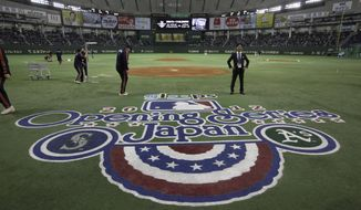 FILE - In this March 28, 2012, file photo, ground staff work prior to the American League season opening Major League Baseball game between the Oakland Athletics and the Seattle Mariners at Tokyo Dome in Tokyo. Oakland and Seattle will play an opening two-game series in Tokyo on March 20 and 21, the fifth time Major League Baseball will start its season in Japan. Oakland will be the home team for both games, Major League Baseball said Tuesday, May 1, 2018.(AP Photo/Shizuo Kambayashi, File)