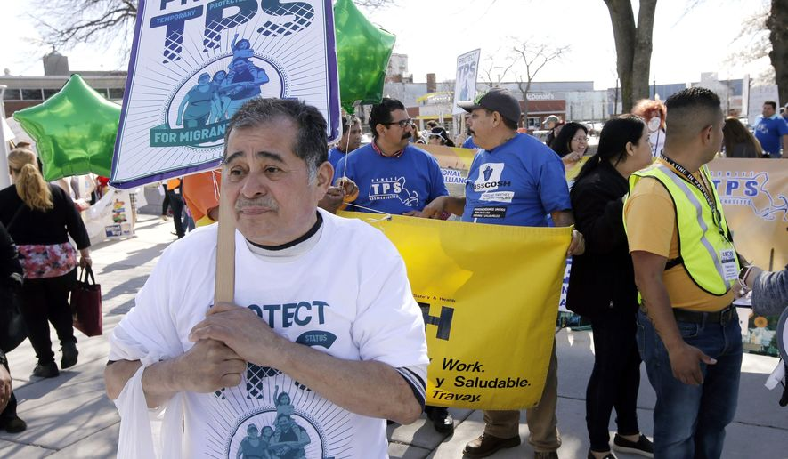 David Oliva, of New Bedford, Mass., marches with other activists, Tuesday, May 1, 2018, in the East Boston section of Boston, to highlight the plight of workers and immigrants, and to call for a higher minimum wage. (AP Photo/Steven Senne)