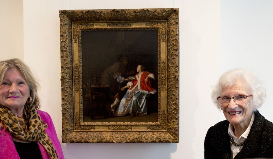 """Ninety-seven-year-old Charlotte Bischoff van Heemskerck, right, and her daughter Rudolphine pose next to the painting """"The Oyster Meal"""" by Jacob Ochtervelt (1634-1682), right, at Sotheby's in Amsterdam, Netherlands, Tuesday, May 1, 2018. The Dutch Old Master painting, belonging to Charlotte's father, was looted by the Nazis in the dying days of World War II and is being put up for auction after it was discovered hanging in the official residence of the Lord Mayor of the City of London and returned late last year to its rightful owners. (AP Photo/Peter Dejong)"""