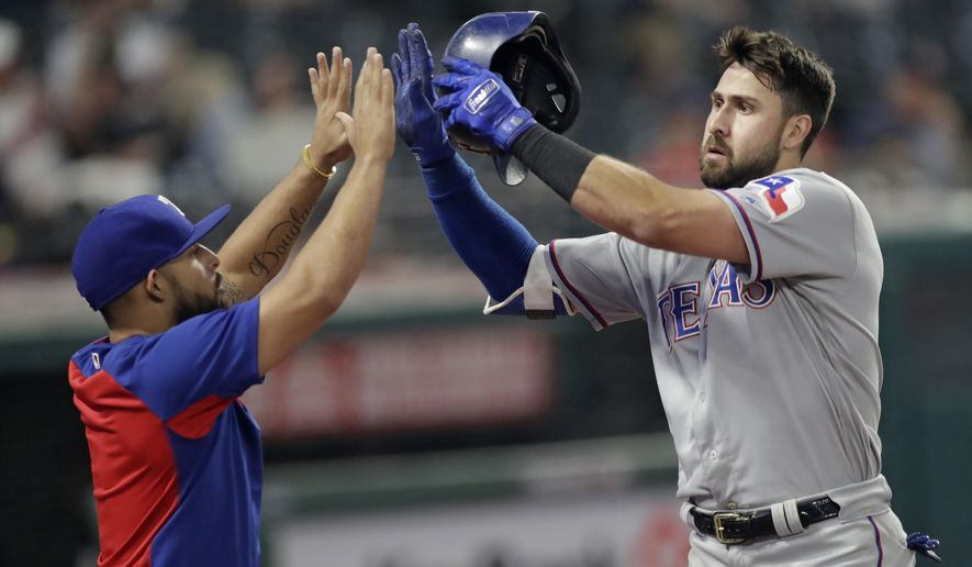 Texas Rangers' Rougned Odor, left congratulates Joey Gallo after Gallo hit a solo home run in the 12th inning of a baseball game against the Cleveland Indians, Tuesday, May 1, 2018, in Cleveland. The Rangers won 8-6. (AP Photo/Tony Dejak)