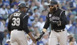 Colorado Rockies' Charlie Blackmon, right, celebrates his home run off Chicago Cubs starting pitcher Kyle Hendricks with third base coach Stu Cole during the first inning of a baseball game Tuesday, May 1, 2018, in Chicago. (AP Photo/Charles Rex Arbogast)