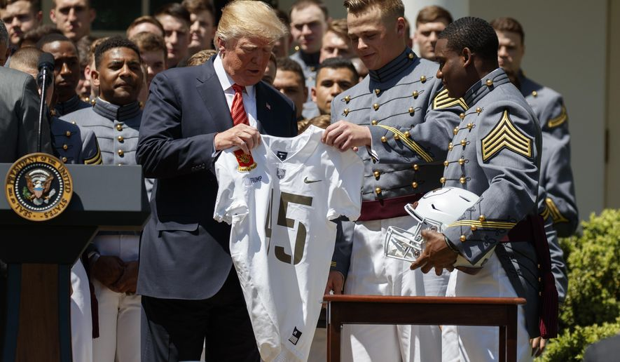 President Donald Trump is presented with a jersey by Ahmad Bradshaw, right, and John Voit, center, during a ceremony to present the Commander in Chief trophy to the U.S. Military Academy football team in the Rose Garden of the White House, Tuesday, May 1, 2018, in Washington. (AP Photo/Evan Vucci)