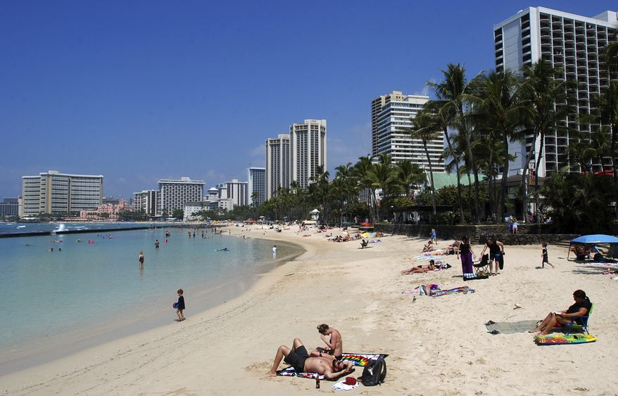 FILE - In this March 13, 2017, file photo, people relax on the beach in Waikiki in Honolulu. Many sunscreen makers could soon be forced to change their formulas or be banned from selling lotions in Hawaii. Hawaii state lawmakers on Tuesday passed a measure that would ban the local sale of sunscreens containing oxybenzone and octinoxate by 2021 in an effort to protect coral reefs.(AP Photo/Caleb Jones, File)