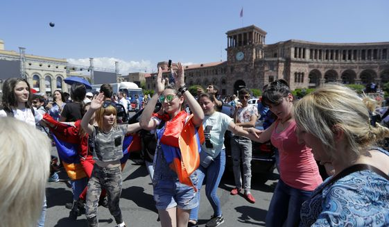 Supporters of opposition lawmaker Nikol Pashinian dance in Republic Square in Yerevan on Wednesday, May 2, 2018. Pashinyan has urged his supporters to block roads, railway stations and airports on Wednesday after the governing Republican Party voted against his election as prime minister. (AP Photo/Sergei Grits)