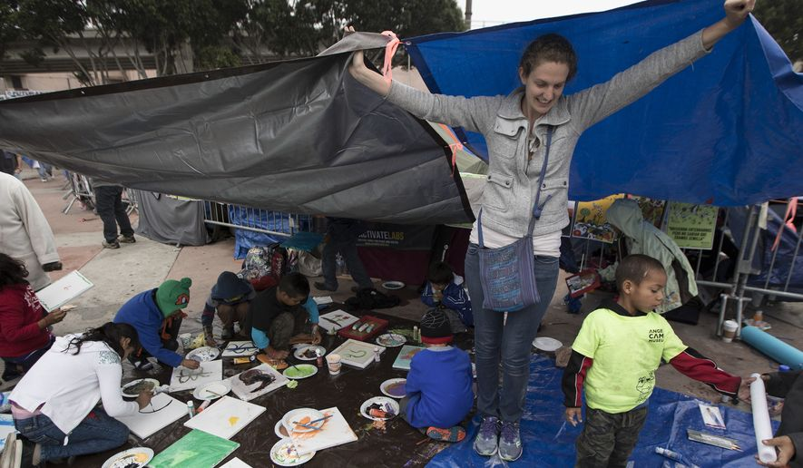 A volunteer holds up tarps to protect children from the rain at the El Chaparral U.S.-Mexico border crossing, in Tijuana, Mexico, Wednesday, May 2, 2018, where the caravan of Central Americans seeking asylum in the United States have set up camp. Some migrants in the caravan of have started what will likely be a long process. About 28 were accepted for processing Monday and Tuesday by U.S. border inspectors at a San Diego crossing. (AP Photo/Hans-Maximo Musielik)