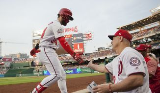 Washington Nationals' Bryce Harper, left, is greeted by bench coach Chip Hale, right, at the dugout after hitting a solo home run off Pittsburgh Pirates starting pitcher Ivan Nova during the first inning of a baseball game at Nationals Park, Wednesday, May 2, 2018, in Washington. (AP Photo/Pablo Martinez Monsivais)