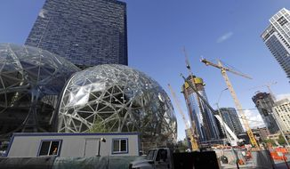 "FILE - In this Wednesday, Oct. 11, 2017, file photo, large spheres take shape in front of an existing Amazon building, behind, as new construction continues across the street in Seattle. Amazon said Wednesday, May 2, 2018, it is pausing construction on a new high-rise building in Seattle while it awaits the outcome of a city proposal to tax worker hours. The Seattle City Council has been weighing a proposed ""head tax"" on high-grossing businesses as a way to raise about $75 million a year for affordable housing and homelessness services. (AP Photo/Elaine Thompson, File)"