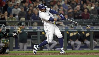 Seattle Mariners' Nelson Cruz hits a three-run home run in front of Oakland Athletics catcher Jonathan Lucroy during the fifth inning of a baseball game Tuesday, May 1, 2018, in Seattle. (AP Photo/Elaine Thompson)