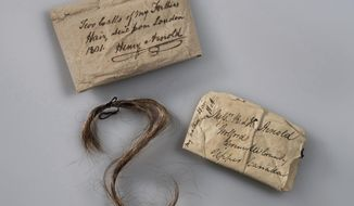 This 2017 photo provided by Fort Ticonderoga shows a lock of Benedict Arnold's hair along with the paper wrappings that have enclosed it, at Fort Ticonderoga, in Ticonderoga, N.Y. The hair will be exhibited for one weekend only, Saturday and Sunday, May 5-6, 2018, at the New York fort Arnold helped capture in opening weeks of the Revolutionary War. The fort's curator said the lock, donated by a direct of descendant of Arnold's in 1952, was wrapped in paper, top, inscribed by Arnold's son Henry and enclosed in another paper, right, addressed to Henry and his brother, who were living in Canada. (Gavin Ashworth/Fort Ticonderoga via AP)
