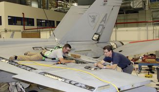 In this Wednesday, April 25, 2018, photo, flight operations mechanic Shawn Edwards, left, removes the left-hand flap shroud from the wing of a 13-year-old F/A-18 Super Hornet in St. Louis. This fighter aircraft, at the end of its original lifespan, was used by the U.S. Navy Gladiators Strike Fighter Squadron based out of Virginia Beach, Va. It is the first Super Hornet of many, set to undergo updates and maintenance to keep it in the fleet for another dozen years. (AP Photo/Ted Shaffrey)