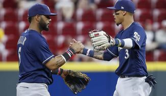 Milwaukee Brewers shortstop Orlando Arcia (3) and second baseman Jonathan Villar celebrate the team's 3-1 win in a baseball game against the Cincinnati Reds, Wednesday, May 2, 2018, in Cincinnati. (AP Photo/John Minchillo)