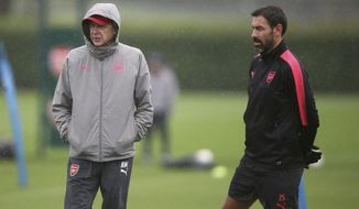 Arsenal manager Arsene Wenger, left, and Robert Pires look on during a training session at London Colney, England, Wednesday May 2, 2018 ahead of their Europa League semifinal second leg match against Atletico Madrid. (John Walton/PA via AP)