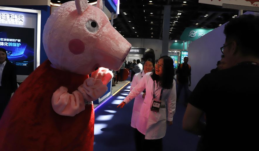 """In this April 27, 2018 photo, a woman reacts to a Peppa Pig mascot during the Global Mobile Internet Conference (GMIC) in Beijing, China. The cherubic British cartoon character, Peppa Pig, has become an unlikely target of China's censors as online fans use her porcine likeness in sardonic memes and """"gangster"""" catchphrases. (AP Photo/Ng Han Guan)"""