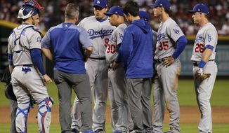 Los Angeles Dodgers starting pitcher Hyun-Jin Ryu, center, talks with a trainer after an injury during the first inning of the team's baseball game against the Arizona Diamondbacks on Wednesday, May 2, 2018, in Phoenix. Ryu left the game. (AP Photo/Matt York)