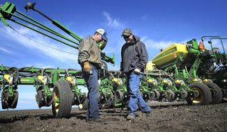 In this Friday, April 27, 2018, photo, contract farmer Bob Dorr and nephew Chad Bergsbaken check the depth made by their planter while working to plant corn in a field behind the family's farm in Avalon, Wis. Dorr likes to keep his income diversified. So doing some custom farm work, by handling necessary tasks such as planting or harvesting for other farmers, just makes sense. (Anthony Wahl/The Janesville Gazette via AP)