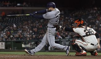 San Diego Padres' Eric Hosmer, left, hits a home run in front of San Francisco Giants catcher Buster Posey during the ninth inning of a baseball game in San Francisco, Tuesday, May 1, 2018. (AP Photo/Jeff Chiu)