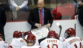FILE - In this March 26, 2017, file photo, Denver head coach Jim Montgomery directs his players during a time-out in the second period of the midwest regional final of the NCAA college hockey tournament in Cincinnati.  A person with knowledge of the situation tells The Associated Press that the Dallas Stars will hire Montgomery to be their next head coach. Montgomery takes over Ken Hitchcock, who retired last month and will become a consultant for the Stars. The person spoke on condition of anonymity Wednesday, May 2, 2018,  because the hiring had not been announced.(AP Photo/John Minchillo, File)