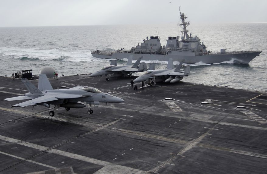 A picture taken Monday, Feb. 13, 2012 shows, a U.S. F-18 fighter jet, left, land on the Nimitz-class aircraft carrier USS Abraham Lincoln (CVN 72) as a U.S. destroyer sells on alongside during fly exercises in the Persian Gulf. The Carrier sailed from the Persian Gulf through the Strait of Hormuz on Tuesday. (AP Photo/Hassan Ammar)