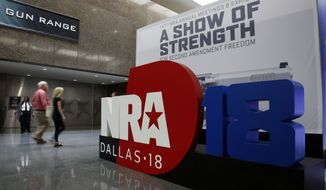 People walk by NRA convention signage in the Kay Bailey Hutchison Convention Center in Dallas, Thursday, May 3, 2018. The convention is scheduled to go through Sunday. (AP Photo/Sue Ogrocki)