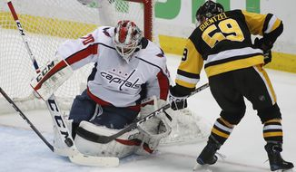 Washington Capitals goaltender Braden Holtby (70) stops a shot by Pittsburgh Penguins' Jake Guentzel (59) during the first period in Game 4 of an NHL second-round hockey playoff series in Pittsburgh, Thursday, May 3, 2018. (AP Photo/Gene J. Puskar)