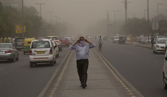 In this Wednesday, May 2, 2018, file photo, a man wraps a scarf around his nose as a dust storm envelops the city in New Delhi, India. Officials said a powerful rainstorm swept parts of north and western India, causing house collapses, toppling trees. (AP Photo/Manish Swarup, File)