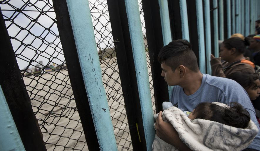 File - In this April 29, 2018 file photo, a member of the Central American migrant caravan, holding a child, looks through the border wall toward a group of people gathered on the U.S. side, as he stands on the beach where the border wall ends in the ocean, in Tijuana, Mexico, Sunday, April 29, 2018. The group that led a monthlong caravan of Central Americans seeking asylum in the United States wanted to draw attention to the plight of people in the violent region. (AP Photo/Hans-Maximo Musielik, File)