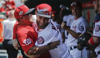 Washington Nationals manager Dave Martinez, left, hugs Bryce Harper, center, in the dugout prior to the start of a baseball game against the Pittsburgh Pirates at Nationals Park, Thursday, May 3, 2018, in Washington. (AP Photo/Pablo Martinez Monsivais) **FILE**