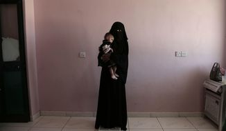 Umm Mizrah, a 25-year-old Yemeni woman, holds her son Mizrah on a scale in Al-Sadaqa Hospital in the southern Yemen city of Aden in this Feb. 13, 2018 photo. Rageh, who is nearly into the second trimester of her pregnancy, weighed 38 kilograms (84 pounds), severely underweight. Mizrah, who was 17 months old, weighed 5.8 kilograms (12.8 pounds), around half the normal weight for his age. (AP Photo/Nariman El-Mofty)