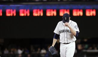 """Seattle Mariners starting pitcher James Paxton gets ready for the next batter after striking out an Oakland Athletics player as a line of """"eh's,"""" a nod to Paxton's Canadian heritage and his strikeout count, appears on a scoreboard during the seventh inning of a baseball game Wednesday, May 2, 2018, in Seattle. (AP Photo/Elaine Thompson)"""