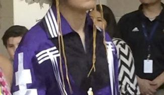 In this May 26, 2016 photo provided by the Gray family, Thomas Kanewakeron Gray walks in a procession during his high school graduation at Santa Fe Indian School in Santa Fe, New Mexico. Gray and his brother Lloyd Skanahwati Gray, were pulled from a Colorado State University admissions tour on Monday, April 30, 2018, after another parent became nervous about their presence and called police. (Gray Family via AP)