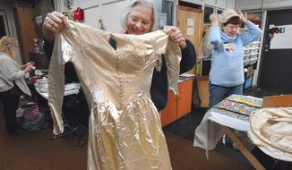 In this April 16, 2018 photo, Leslie Frizzell left, and Kay Brook measure up a wedding dress  that was donated to Fibers of Love in Bloomington, Ill. The dress will be cut up and made into burial gowns for stillborn infants by the group.About 50 women in the Fibers of Love group come together every Monday from April through December in Bloomington to spend the day creating items for social service agencies in Central Illinois and around the world. the group have used their talent to touch thousands of lives over 25 years with gifts of dignity, warmth and comfort. (David Proeber/The Pantagraph via AP)
